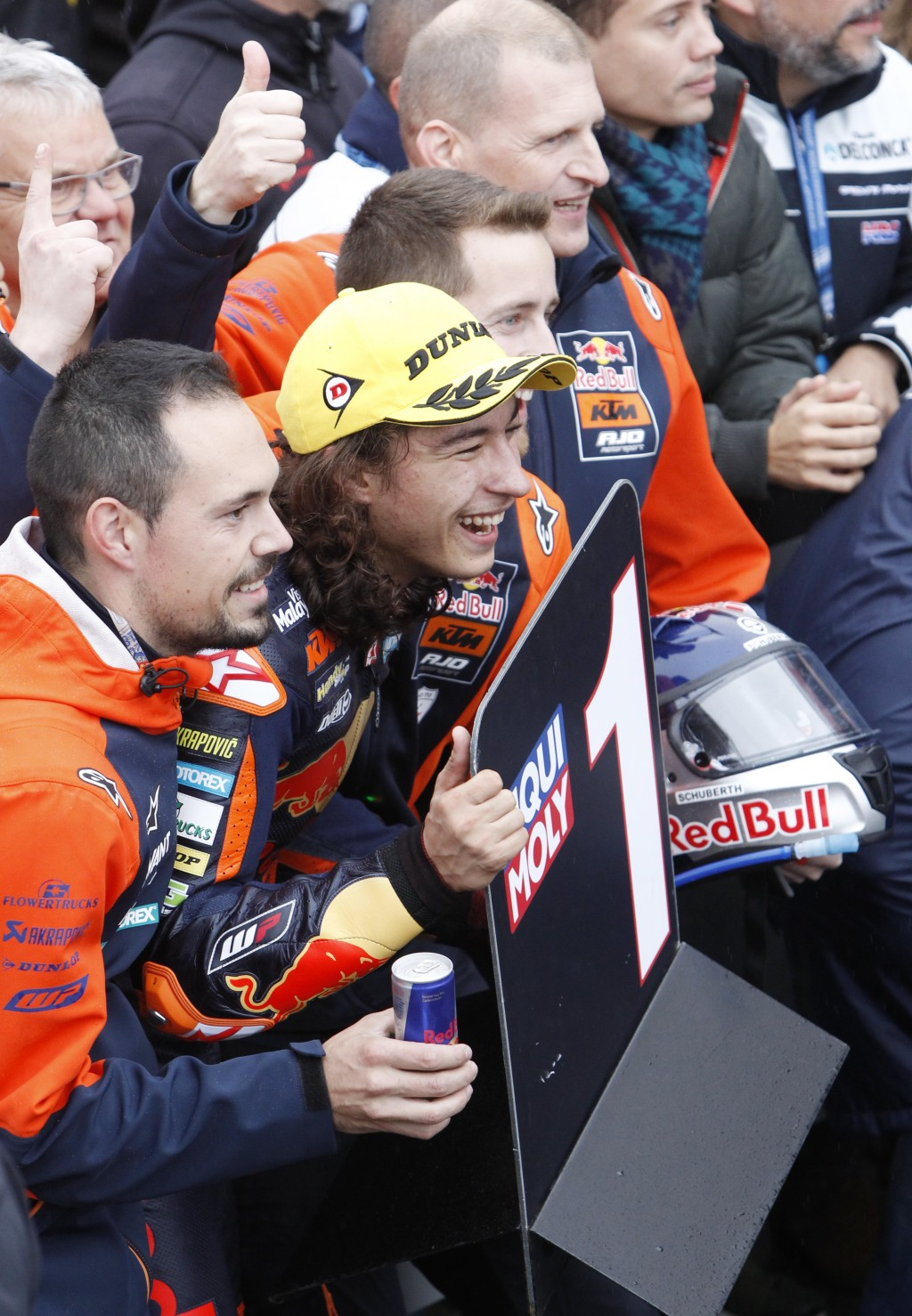 Moto3 KTM rider Can Oncu of Turkey, centre, celebrates with team members after winning the Moto3 Motorcycle Grand Prix at the Ricardo Tormo circuit in