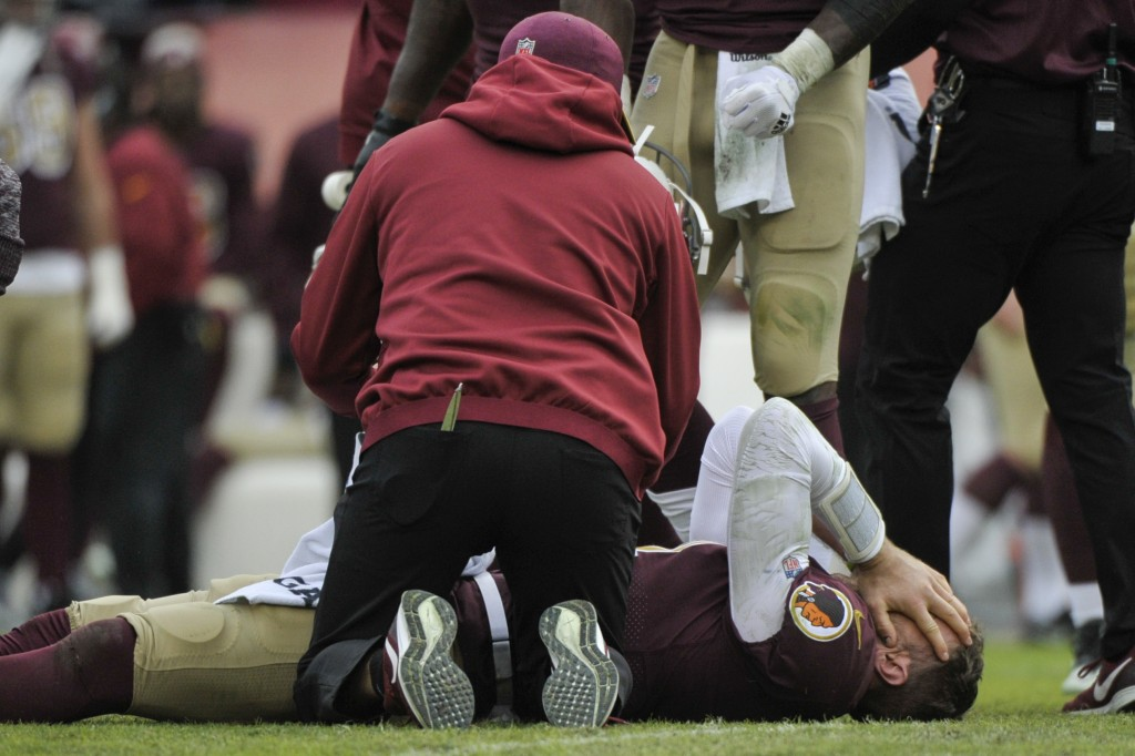 Washington Redskins quarterback Alex Smith, bottom, reacts after an injury during the second half of an NFL football game against the Houston Texans, ...