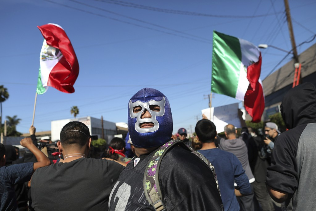"""An anti-migrant demonstrator sporting a """"Lucha Libre"""" wrestling mask attends a protest against the presence of thousands of Central American migrants"""