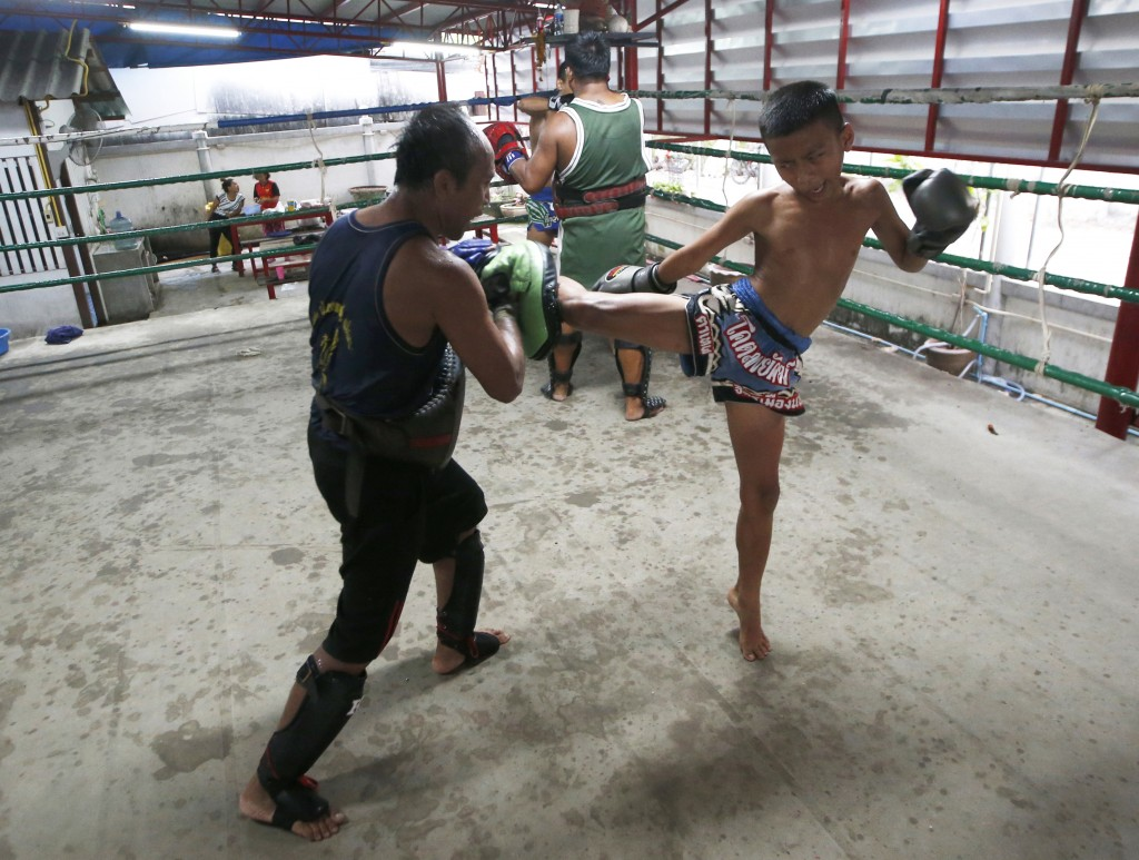 In this Wednesday, Nov. 14, 2018, photo, Thai kickboxer Chaichana Saengngern, 10-years old, practices kicks at a training camp in Bangkok, Thailand. T...