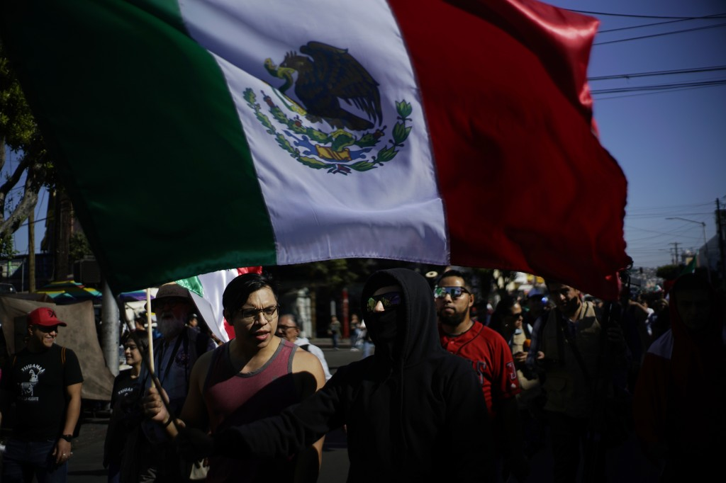 A demonstrator carries a Mexican flag during a protest against the presence of thousands of Central American migrants in Tijuana, Mexico, Sunday, Nov.