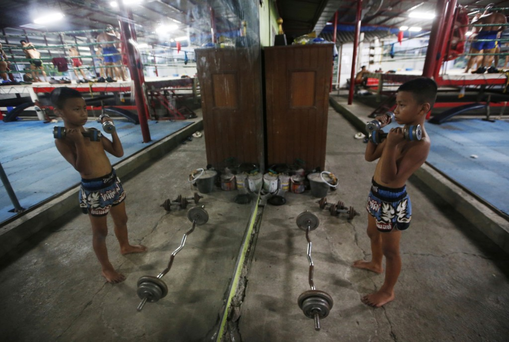 In this Wednesday, Nov. 14, 2018, photo, Thai kickboxer Chaichana Saengngern, 10-years old, practices lifting dumbbell at training camp Bangkok, Thail...