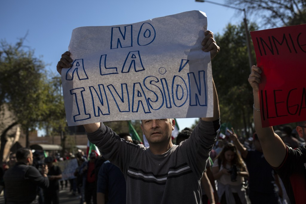 """A demonstrator with a sign that reads in Spanish: """"No to the invasion"""" protests the presence of thousands of Central American migrants in Tijuana, Mex..."""