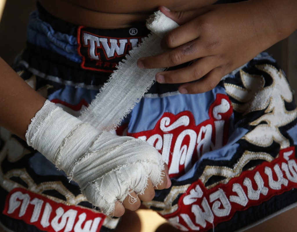 In this Wednesday, Nov. 14, 2018, photo, Thai kickboxer Chaichana Saengngern, 10-years- old, wraps his fists before practice at a training camp in Ban