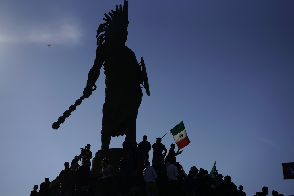 Demonstrators stand under an indigenous statue of Aztec ruler Cuauhtemoc as they protest the presence of thousands of Central American migrants in Tij...