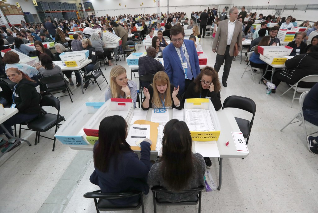 FILE- In this Friday, Nov. 16, 2018, file photo workers at the Broward County Supervisor of Elections office show Republican and Democrat observers ba