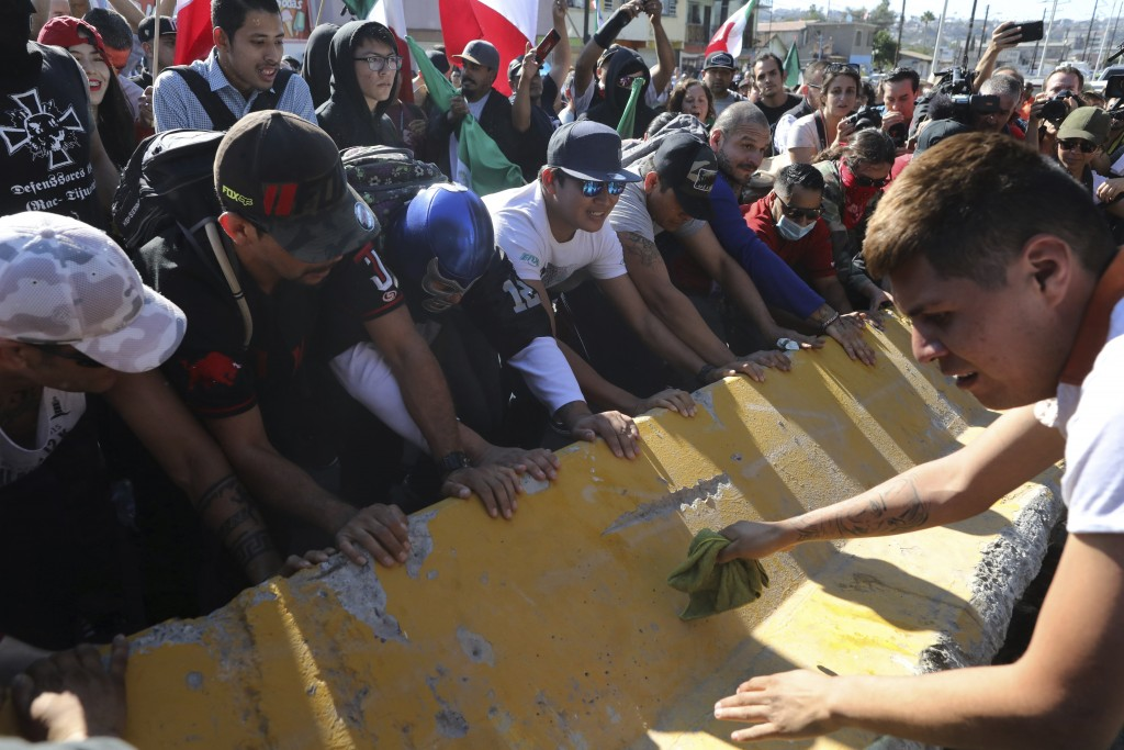 Demonstrators turn over a barrier wall protecting a migrant shelter as they protest the presence of thousands of Central American migrants in Tijuana,...