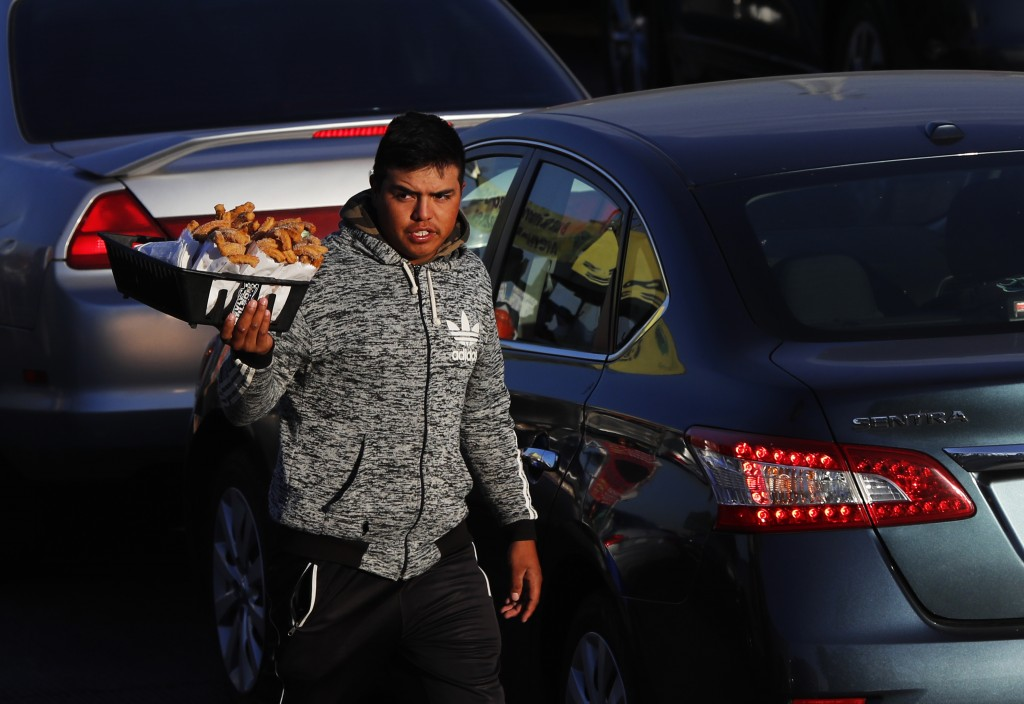 """A vendor sells """"churros,"""" a deep-fried snack, to drivers waiting in line to leave Tijuana, Mexico and enter the U.S., Sunday, Nov. 18, 2018. While man"""