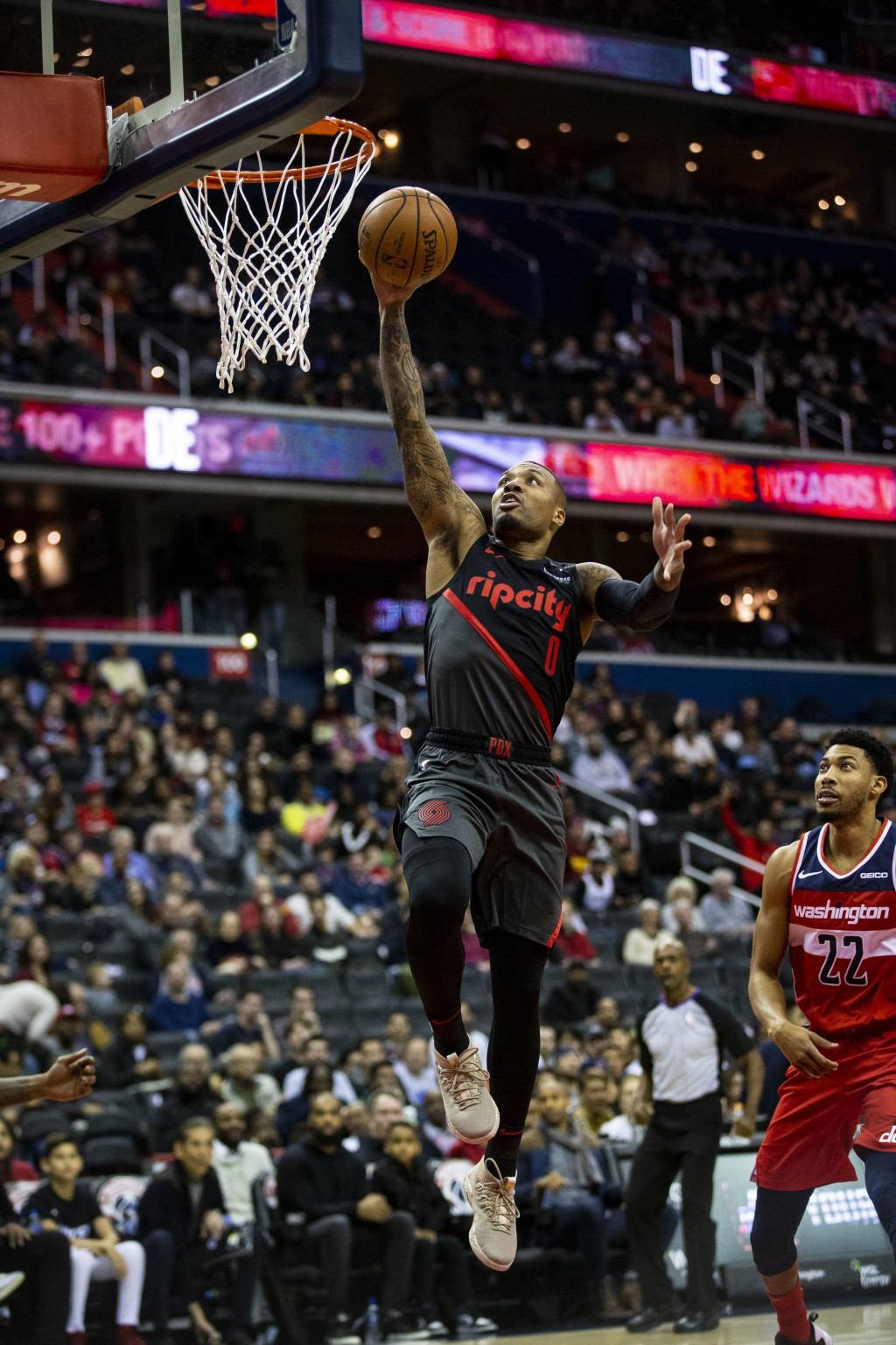 Portland Trail Blazers guard Damian Lillard (0) makes a layup past Washington Wizards forward Otto Porter Jr. (22) during the first half of an NBA bas