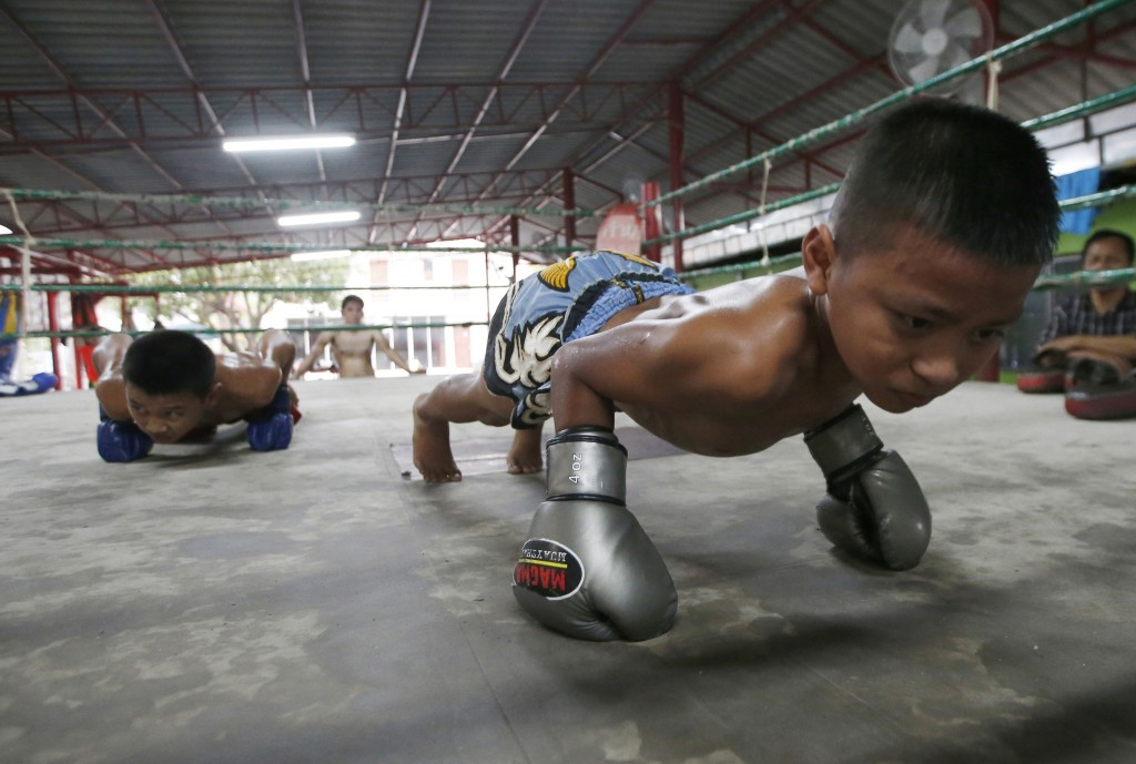 In this Wednesday, Nov. 14, 2018, photo, Thai kickboxer Chaichana Saengngern, right, 10- years old, does pushups at in the ring at a training camp in ...