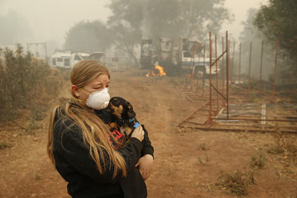 In this Nov. 10, 2018, photo, Arianne Harvey holds her dog T.J. near a truck still on fire from the Camp Fire in Paradise, Calif. Harvey was living in...