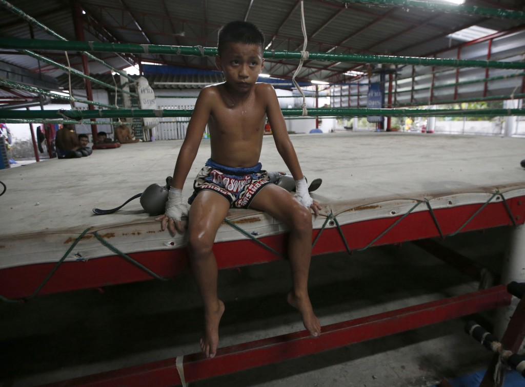 In this Wednesday, Nov. 14, 2018, photo, Thai kickboxer Chaichana Saengngern, 10 years old, rests after practice on the mat at a training camp in Bang