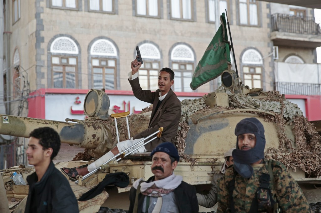 FILE - In this Dec. 4, 2017, file photo, Houthi Shiite fighters guard a street leading to the residence of former Yemeni President Ali Abdullah Saleh,