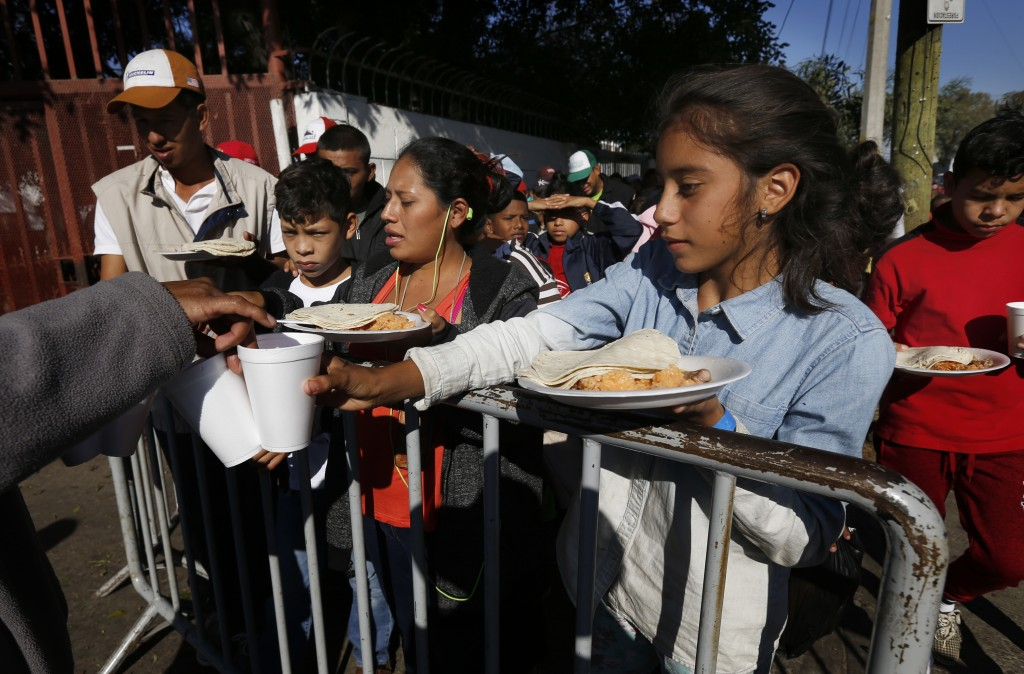 Central American migrants eat a free breakfast outside a shelter for migrants in Tijuana, Sunday, Nov. 18, 2018. While many in Tijuana are sympathetic