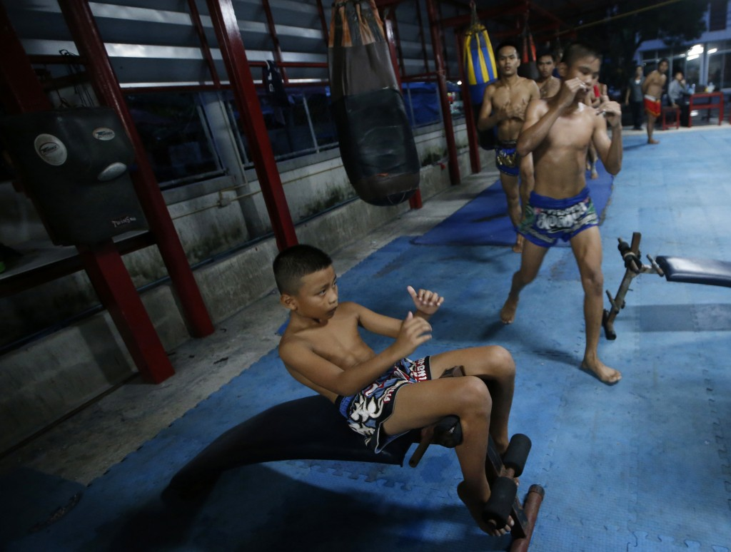 In this Wednesday, Nov. 14, 2018, photo, Thai kickboxer Chaichana Saengngern, 10-years old, practices sit up bench exercises at training at camp Bangk...