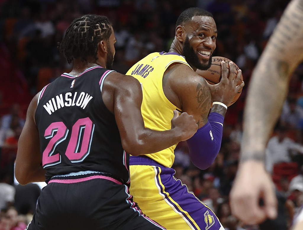 Los Angeles Lakers forward LeBron James keeps the ball from Miami Heat forward Justise Winslow during the first half of an NBA basketball game Sunday,...