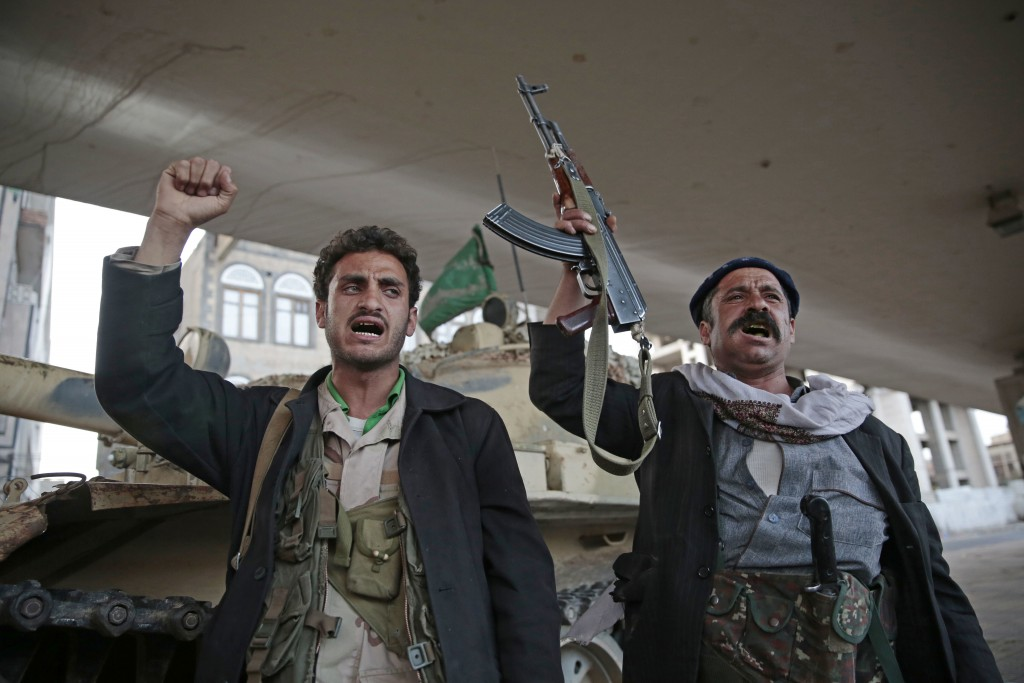 FILE - In this Dec. 4, 2017, file photo, Houthi Shiite fighters chant slogans as they guard a street leading to the residence of former Yemeni Preside...