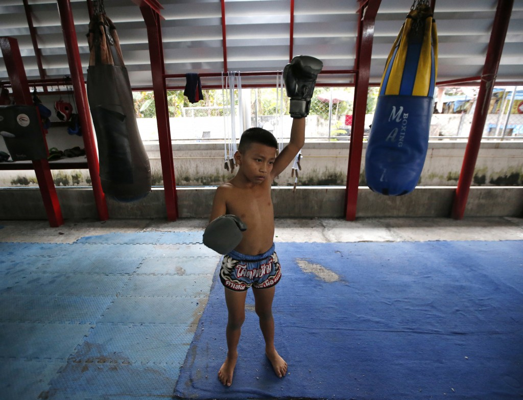 In this Wednesday, Nov. 14, 2018, photo, Thai kickboxer Chaichana Saengngern, 10-years old, warms up at a training camp in Bangkok, Thailand. Thai law...