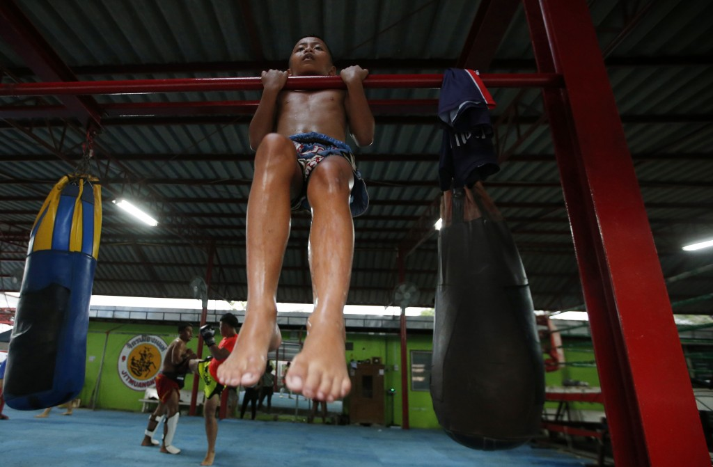 In this Wednesday, Nov. 14, 2018, photo, Thai kickboxer Chaichana Saengngern, 10-years old, does pull-ups at a training camp in Bangkok, Thailand. Tha
