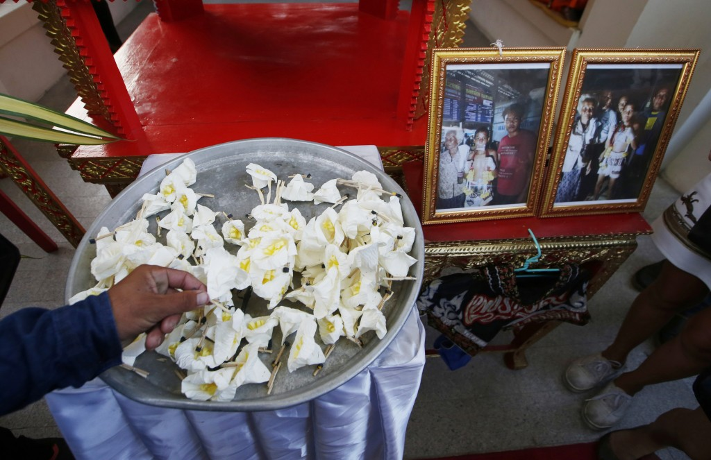In this Thursday, Nov. 15, 2018, photo, mourners lay flowers at the coffin of 13-year-old Thai kickboxer Anucha Tasako during his funeral services at