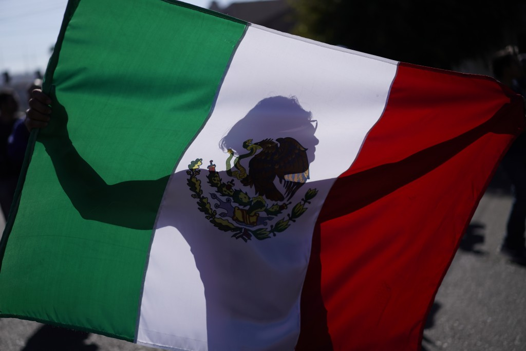 A demonstrator holds a Mexican flag outside a migrant shelter to protest the presence of thousands of Central American migrants in Tijuana, Mexico, Su...