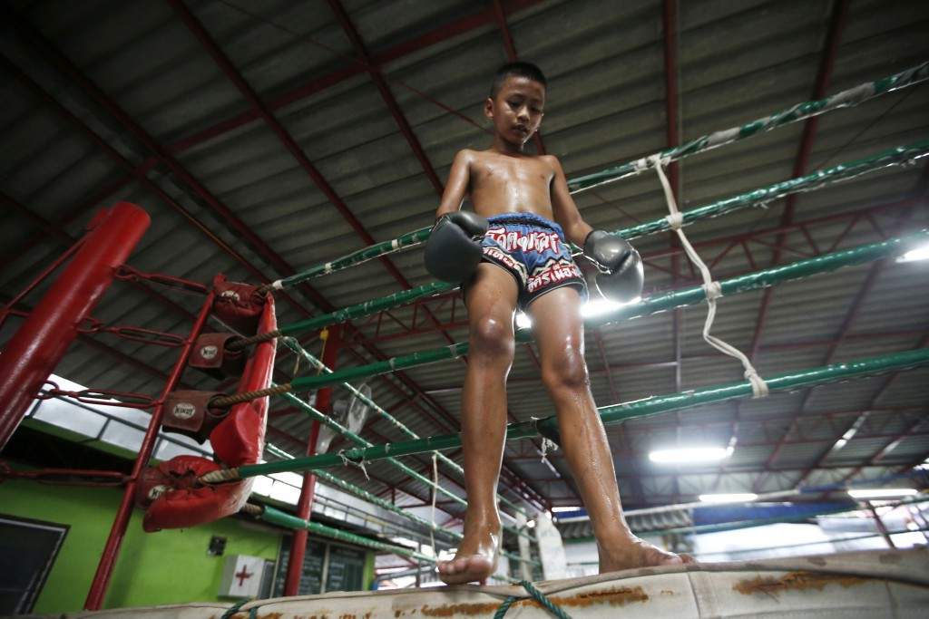 In this Wednesday, Nov. 14, 2018, photo, Thai kickboxer boxer Chaichana Saengngern, 10-years old, stand on the ring after of practices at a training c...