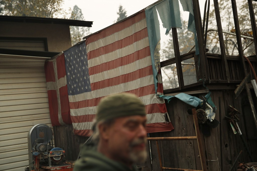In this Nov. 15, 2018, photo, Brad Weldon stands near flags adorning his home in Paradise, Calif. Weldon, who saved his Paradise home from the fire, s...