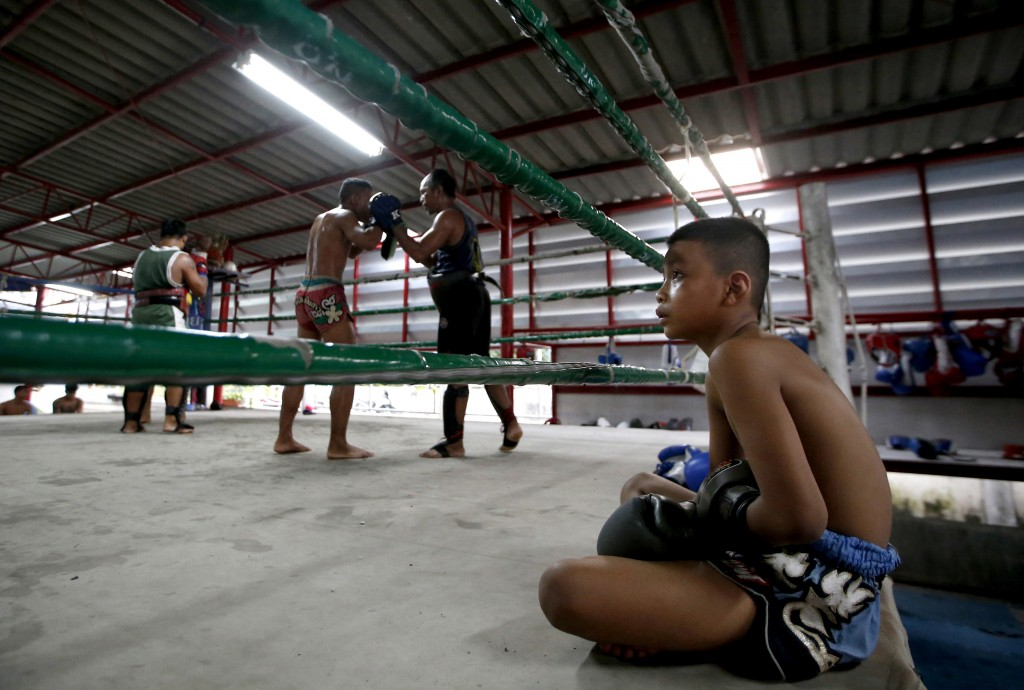 In this Wednesday, Nov. 14, 2018, photo, Thai kickboxer Chaichana Saengngern, 10-years old, watch their boxer training on boxing ring at training at c...