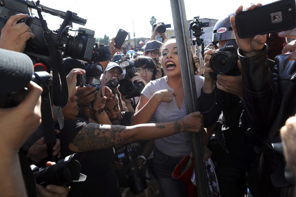 An anti-migrant demonstrator is surrounded by the press as she argues with a woman during a protest against the presence of thousands of Central Ameri...