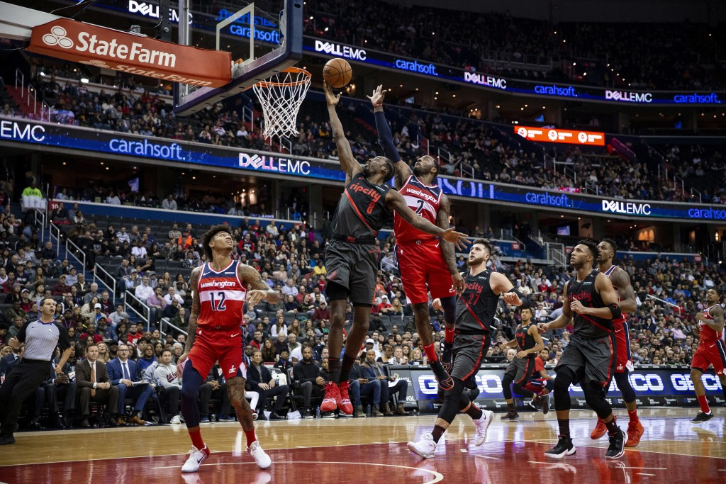Portland Trail Blazers forward Al-Farouq Aminu (8) goes for a layup past Washington Wizards guard John Wall (2) and forward Kelly Oubre Jr. (12) durin