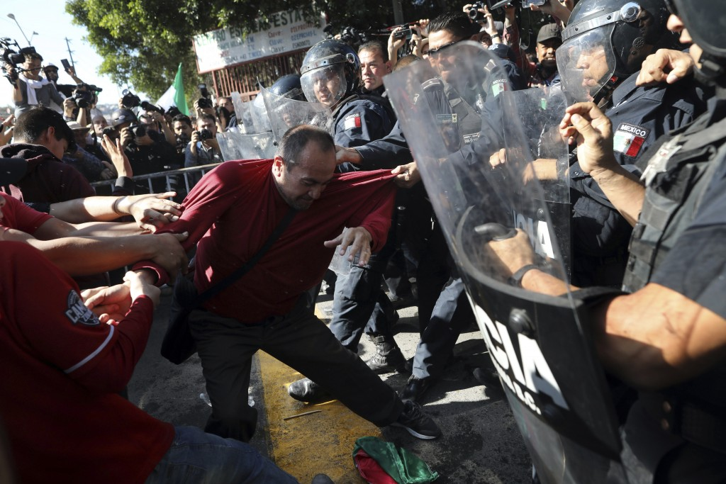 Demonstrators clash with police outside a migrant shelter as they protest the presence of thousands of Central American migrants in Tijuana, Mexico, S