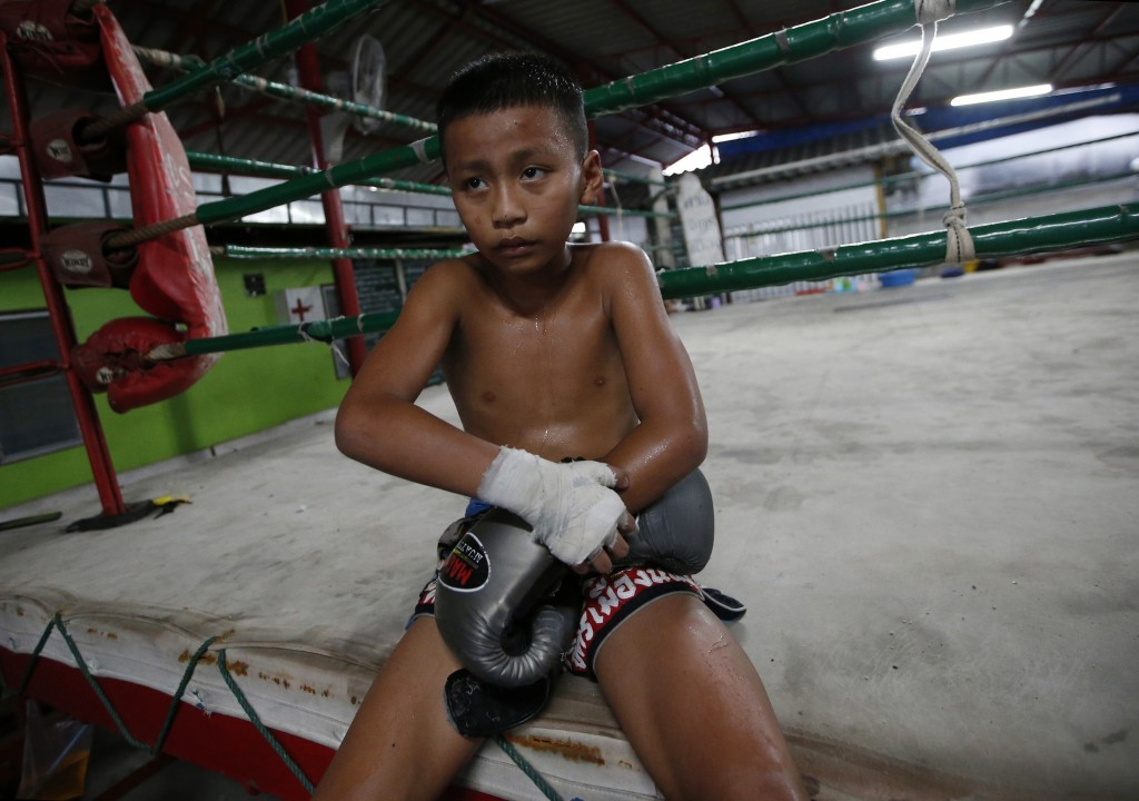In this Wednesday, Nov. 14, 2018, photo, Thai kickboxer Chaichana Saengngern, 10-years old, take off his boxing gloves after practice at a training ca...
