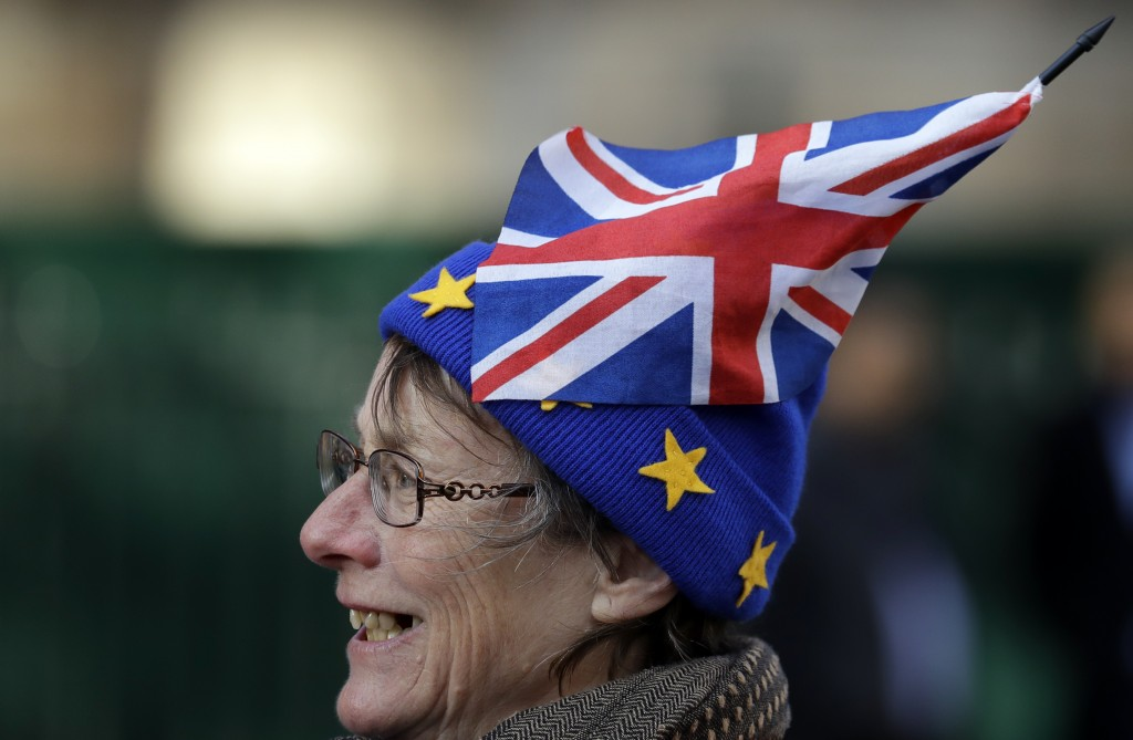 An Anti Brexit campaigner smiles as she demonstrates in Westminster in London, Monday, Nov. 19, 2018.  The EU nations and Britain are still negotiatin
