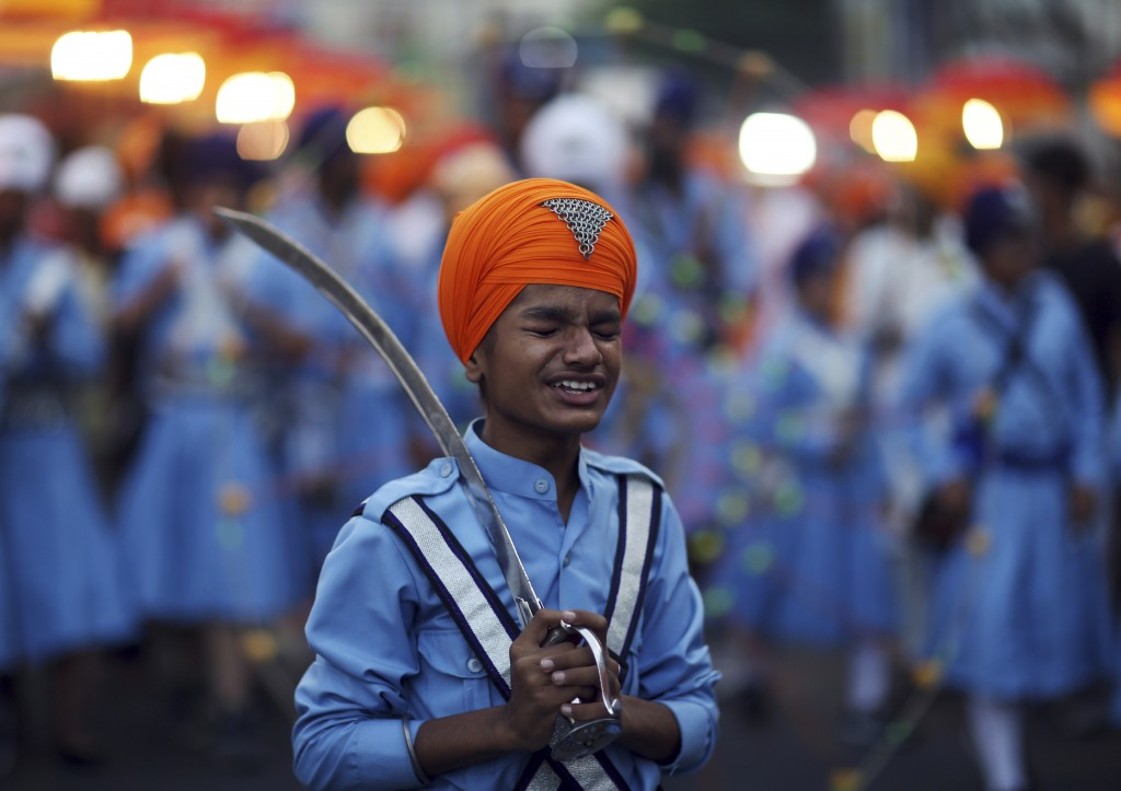 In this Nov. 19, 2018, photo, a Sikh boy reacts to a jovial comment from another as he prepares to display his martial art skills during a religious p...
