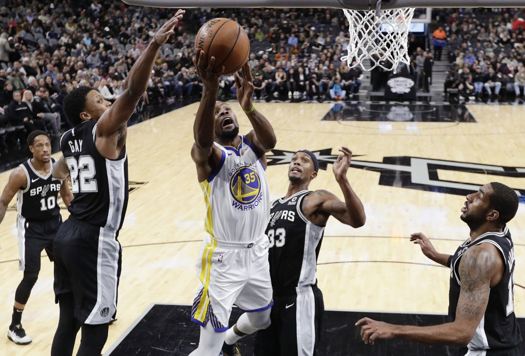 Golden State Warriors forward Kevin Durant (35) drives to the basket past San Antonio Spurs forward Rudy Gay (22) and forward Dante Cunningham (33) du
