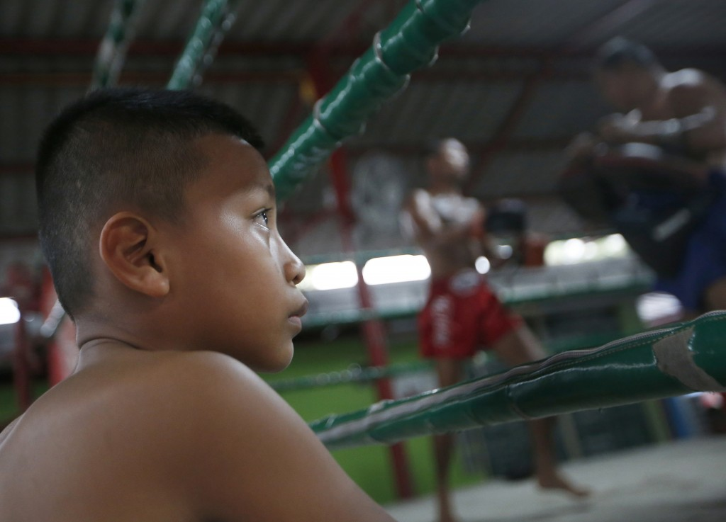 In this Wednesday, Nov. 14, 2018, photo, Thai kickboxer Chaichana Saengngern, 10-years old, watch other boxers train in the ring at a training camp in...