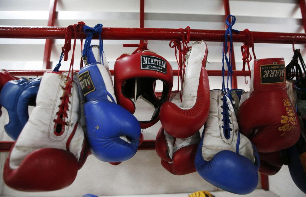 In this Wednesday, Nov. 14, 2018, photo, Thai kickboxing gloves and headgear hang at a training camp in Bangkok, Thailand. Thai lawmakers recently sug...