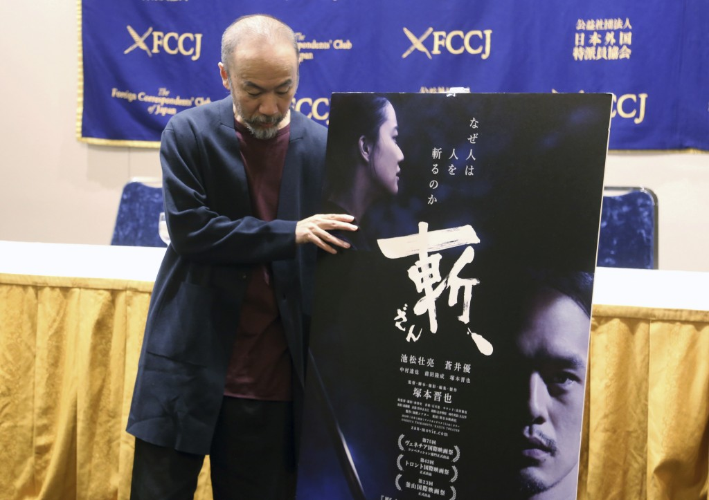 "In this Nov. 7, 2018, photo, Japanese director Shinya Tsukamoto holds a banner about his latest film ""Killing"" during a press conference in Tokyo. He"