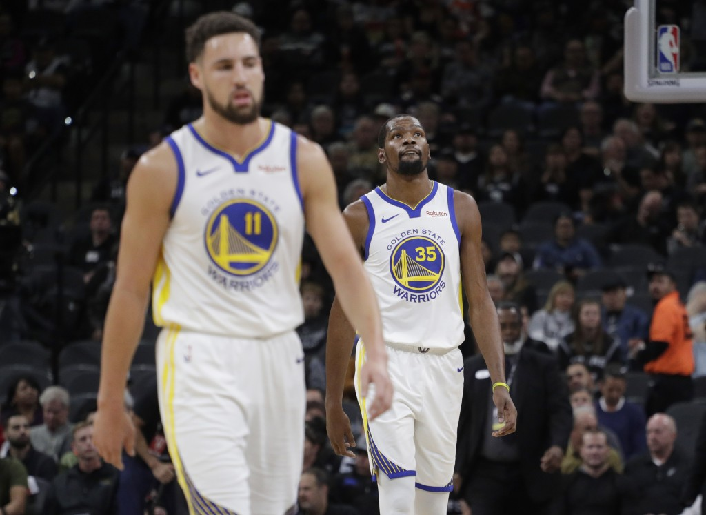 Golden State Warriors forward Kevin Durant (35) and guard Klay Thompson (11) walk off the court during a timeout during the first half of an NBA baske...