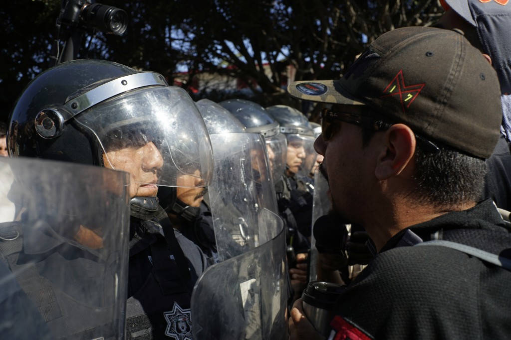 Police stand guard to protect a migrant shelter as demonstrators protest the presence of thousands of Central American migrants in Tijuana, Mexico, Su...