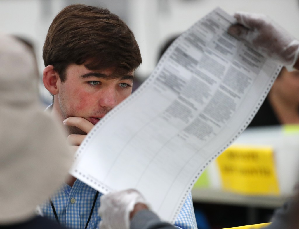 FILE- In this Friday, Nov. 16, 2018, file photo a Republican observer looks at a ballot during a hand recount at the Broward County Supervisor of Elec