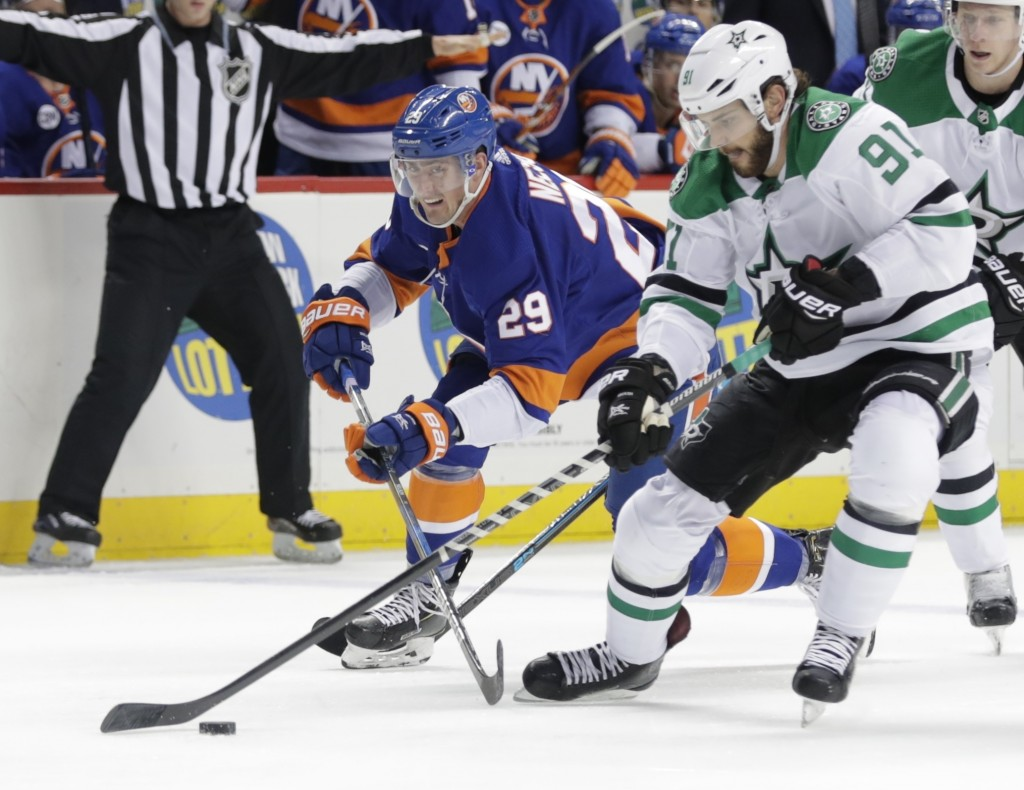 Dallas Stars' Tyler Seguin (91) fights for control of the puck with New York Islanders' Brock Nelson (29) during the second period of an NHL hockey ga