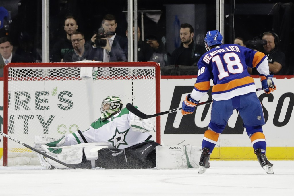 New York Islanders' Anthony Beauvillier (18) shoots the puck past Dallas Stars goaltender Ben Bishop during the first period of an NHL hockey game Sun