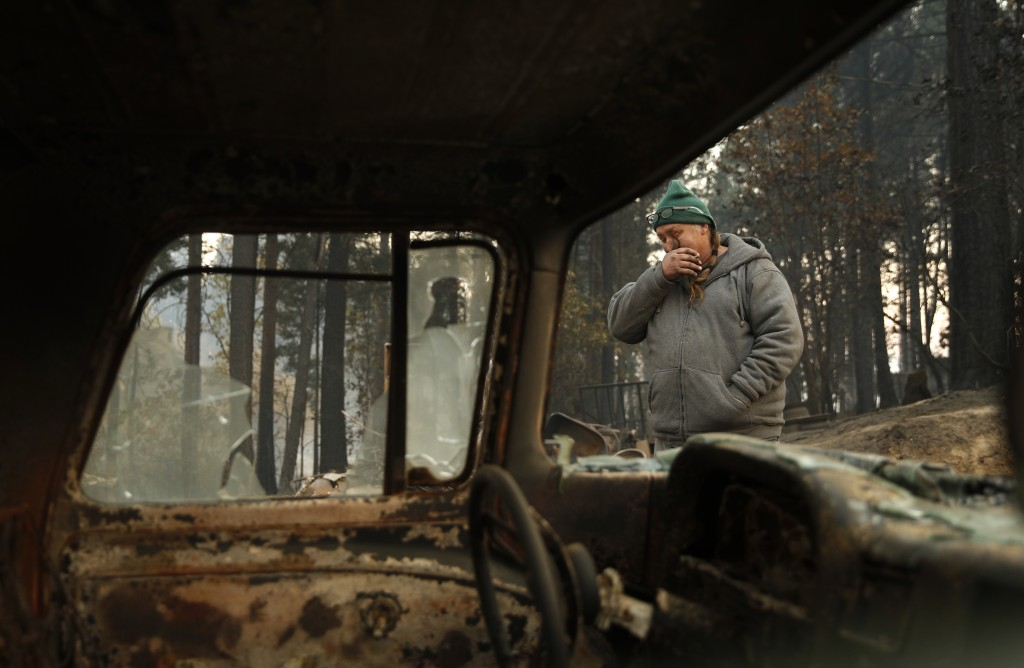 In this Nov. 15, 2018, photo, Troy Miller wipes his eyes as he walks beside a burned out car on his property in Concow, Calif. Miller said he tried to...