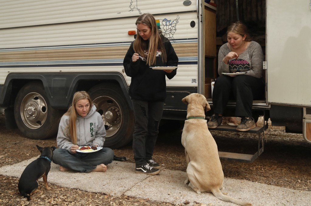 In this Nov. 14, 2018, photo, sisters Arissa Harvey, from left, Araya Cipollini, and Arianne Harvey eat beside an RV they are living in near their hom...