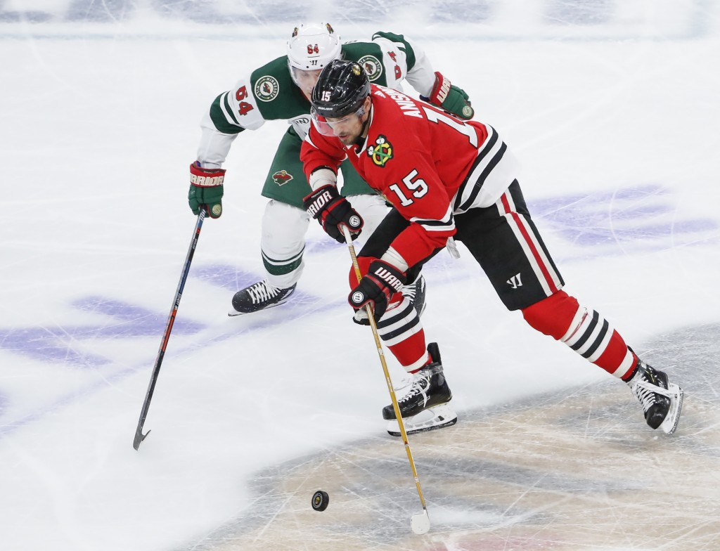 Chicago Blackhawks center Artem Anisimov (15) battles for the puck with Minnesota Wild right wing Mikael Granlund (64) during the third period of an N...