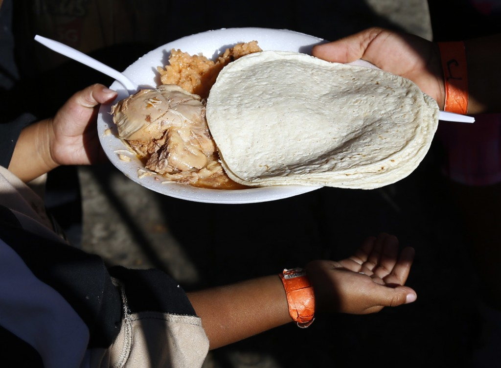 A young Central American migrant receives a free meal of chicken, rice and tortillas at a shelter for migrants in Tijuana, Sunday, Nov. 18, 2018. Whil