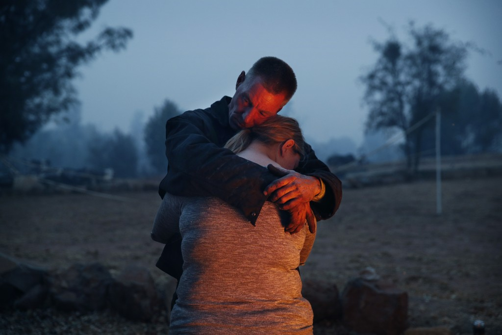 In this Nov. 14, 2018, photo, Phillip Harvey embraces his daughter Arianne Harvey as they stay warm beside a fire in Paradise, Calif. The family lost ...
