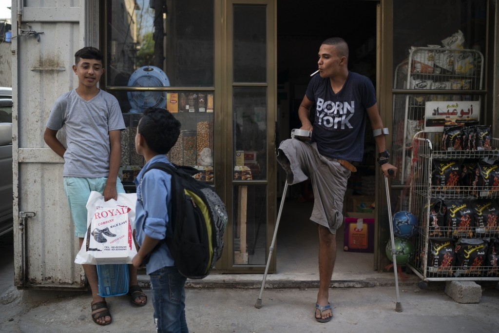 In this Sept. 16, 2018 photo, Atalla Fayoumi, smokes a cigarette outside a shop near his house in Gaza City. The 18-year-old Palestinian's right leg w...