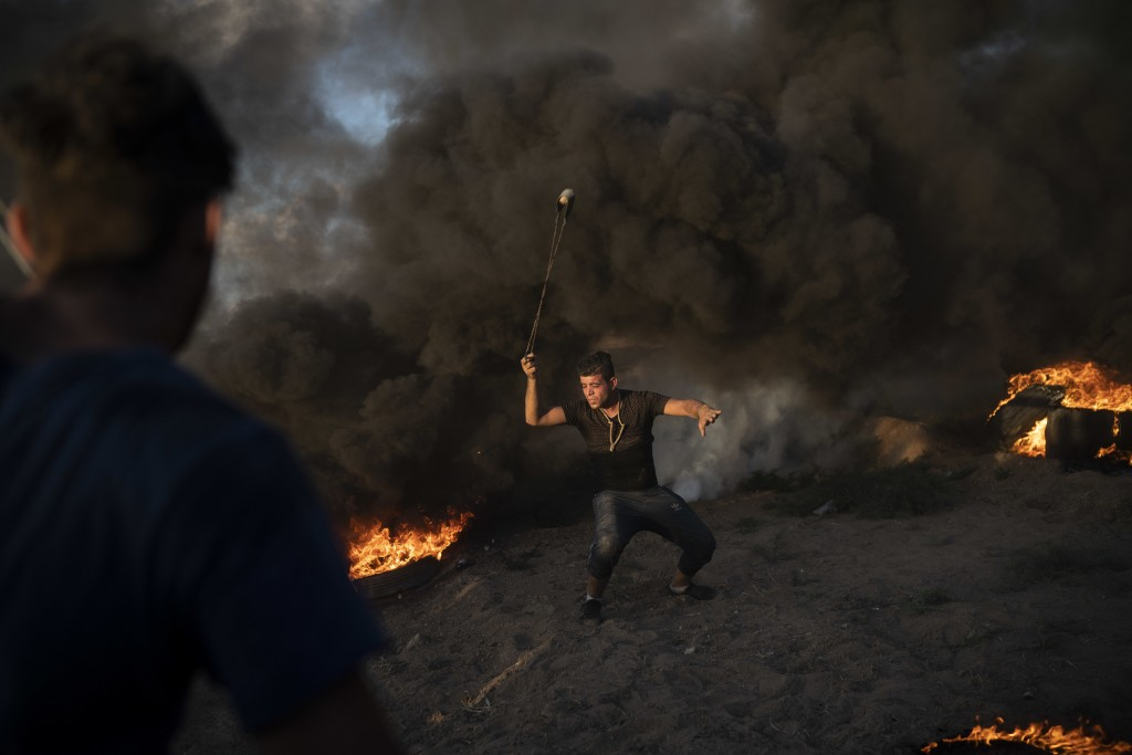 In this Friday, Sept. 7, 2018 photo, A Palestinian protester hurls stones during a protest at Gaza Strip's border with Israel, east of Gaza City. The ...